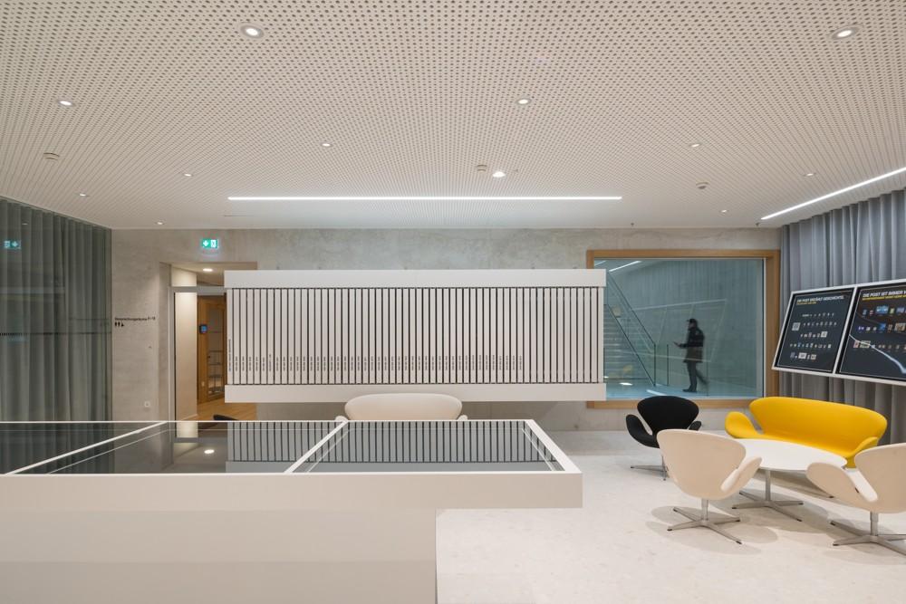 Post am RochuDie Lounge wird durch das modulare LED-Beleuchtungssystem INTRO beleuchtet – mit in der Akustikdecke eingebauten Einzelstrahlern sorgt es für ein klares Allgemeinlicht. Ergänzt wird es durch in die Decke eingebaute SLOTLIGHT-Lichtlinien. Abbildung: Zumtobel/Lukas Schaller