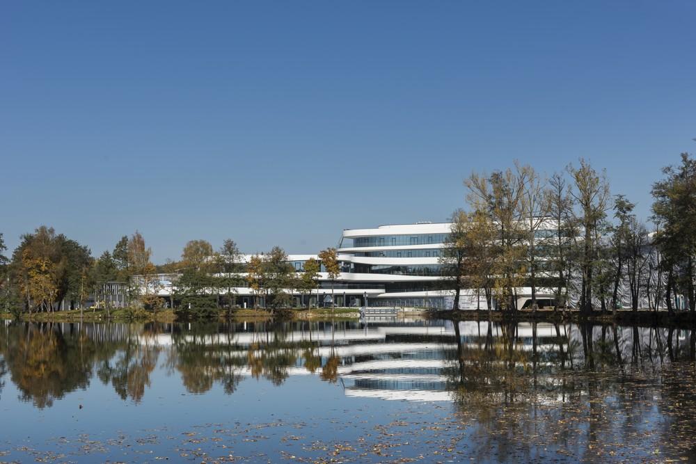 Sensibel fügt sich der fünfgeschossige Neubau in die weitläufige Parklandschaft mit eigenem Weiher ein. Abbildung: Uwe Mühlhäusser