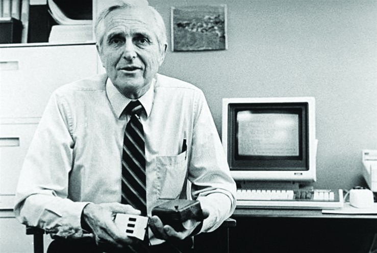 Der Erfinder der Maus, Doug Engelbart, hält in der linken Hand seine erste Maus von 1963 und in der rechten eine aus dem Jahr 1984. Abbildung: Kelson