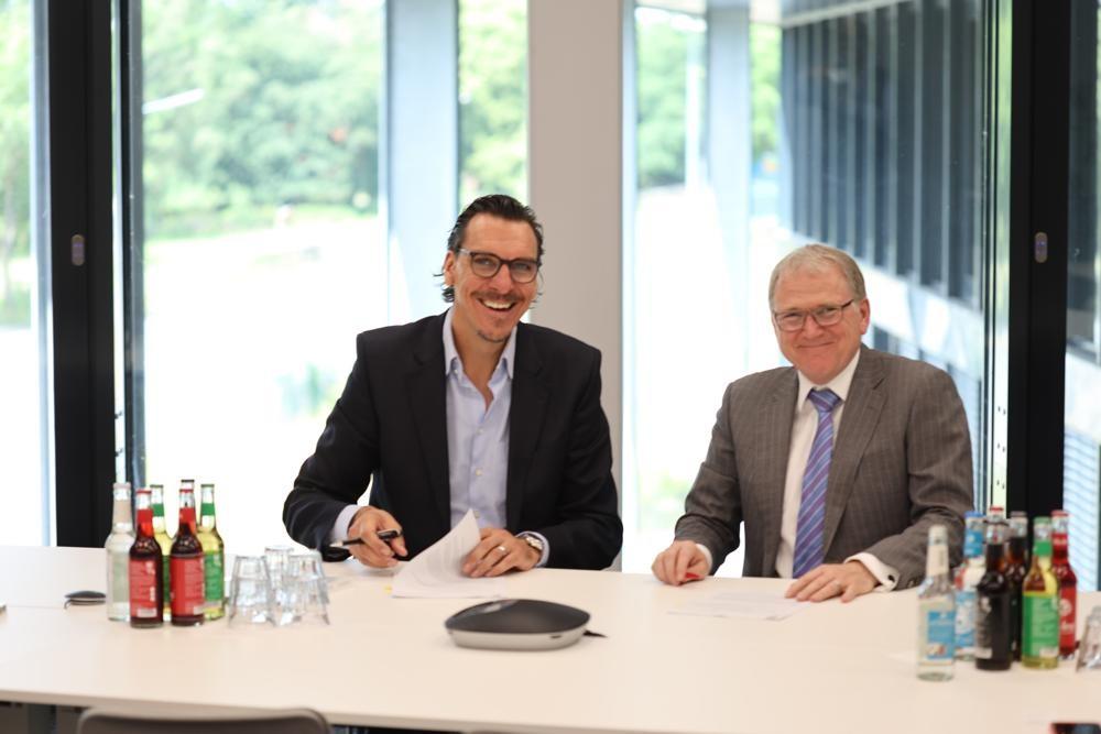 A. Hahn (Deutsche Lichtmiete, links) und S. Sallinger (Artemide) bei der Vertragsunterzeichnung. Abbildung: Artemide