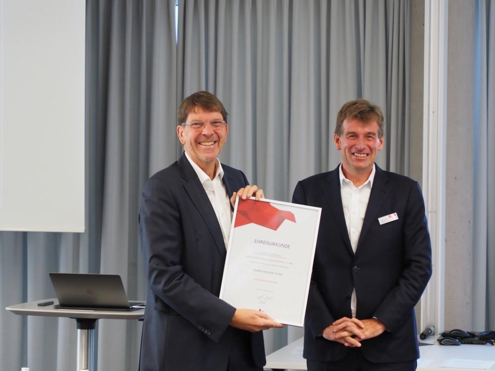 Hendrik Hund (links) bekommt von Helmut Link die Ernennungsurkunde zum Ehrenvorsitzenden des IBA überreicht. Abbildung: IBA